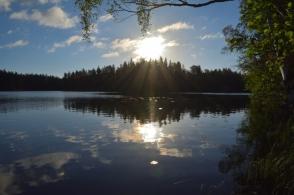 Sol över stilla sjö